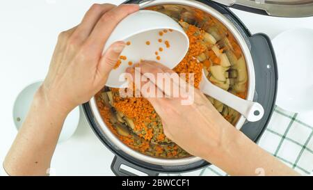 Red lentils, green lentils, and some ingredients close up in a pot. Multi cooker lentil soup rscipe - Stock Photo