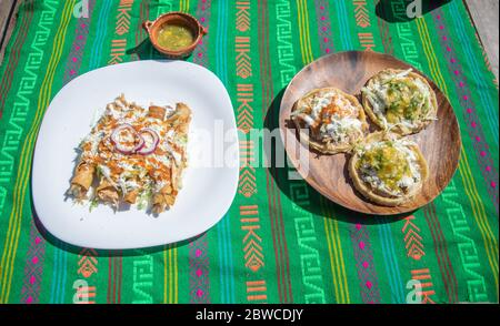 variety of Mexican food dishes. sopes, tacos, gorditas stuffed. on mexican serape - Stock Photo