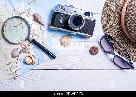 Top view of planning vacation planning using a map, magnifier, retro camera - Travel influencer looking for the next travel destination - Concept of a