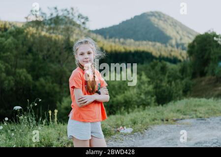 On a sunny day, a portrait of a beautiful young tourist girl, with a backpack, fashion woman, walks through the forest, the background of trees. Concept: recreation, beautiful view, sports, travel - Stock Photo
