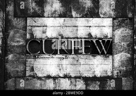 Photo of real authentic typeset letters forming Curfew text on vintage textured monochrome silver grunge background