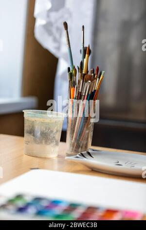 Art brushes for painting in a glass cup on the desktop. - Stock Photo