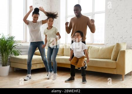 African couple and little kids having fun dancing at home