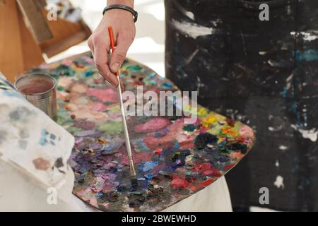 Close up of unrecognizable male artist mixing paint on palette while painting in art studio, copy space