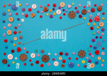 Multi-colored buttons are scattered on the table, a needle. Accessories for sewing. Top view with copy space, flat lay. - Stock Photo