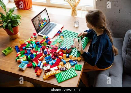 Girl playing with constructor at home, watching teacher's online tutorial on laptop. Digitalization, remote education concept. Technologies and devices. Man showing, giving online lesson. Artwork.