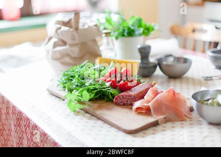 Kitchen table with ingredients for preparing pizza. Cooking process at home Vegetables cheese greens - Stock Photo