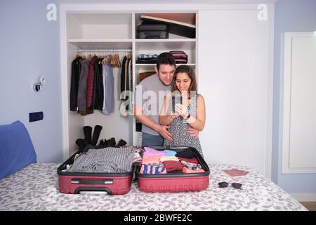 Young caucasian couple looking at the smartphone smiling, preparing a travel. Passports and sun glasses on the bed. Packing concept. Stock Photo