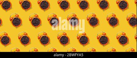coffee beans in orange alarm clock on bright yellow background. Pattern - Stock Photo