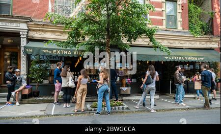 "Customers take advantage of relaxed liquor laws and ""grab and go"" cocktails in front of a restaurant in Greenwich Village in New York on a  warm Memorial Day Weekend on Sunday, May 24, 2020. (© Richard B. Levine) - Stock Photo"