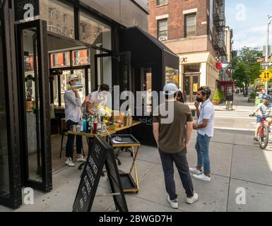 "Customers take advantage of relaxed liquor laws and ""grab and go"" cocktails in front of a restaurant in Soho in New York on a  warm Memorial Day Weekend on Sunday, May 24, 2020. (© Richard B. Levine) - Stock Photo"