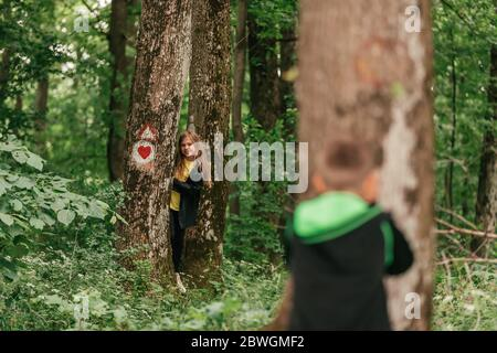 Little boy and cute girl playing hide and seek in forest,  spending good time in spring nature. - Stock Photo
