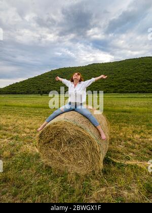 Countryside style 40s forties woman riding sitting seated big hay bale in field cheerful with spread spreading hands legs arms barefeet bare feet foot - Stock Photo