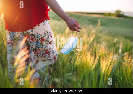 Close up of unrecognizable woman walking outdoors throwing away her mask. Young happy girl removing protective mask. End of pandemic coronavirus concept. Meadow landscape, Pollen allergy at spring . - Stock Photo