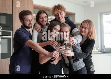 Group of smiling friends having drinks in the kitchen - Stock Photo