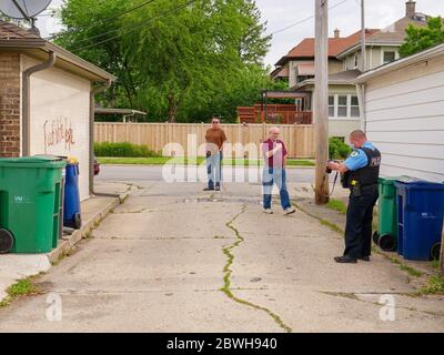 Oak Park, Illinois. 1st June 2020. An Oak Park Police evidence technician investigates racist graffiti that appeared overnight on some garages on the north side of this Chicago suburb. Evidently, the purpetrators knew who lived on each tagged property as both anti-white and anti-black graffiti was used on selected properties and varied with the race of the homeowners. - Stock Photo