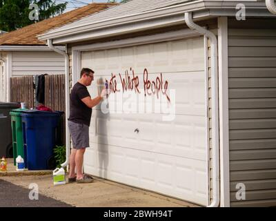 Oak Park, Illinois. 1st June 2020. A homeowner cleans racist graffiti from his garage door. The grafitti appeared overnight on the north side of this Chicago suburb. Evidently, the purpetrators knew who lived on each tagged property as both anti-white and anti-black grafitti was used on selected properties and varied with the race of the homeowners. - Stock Photo