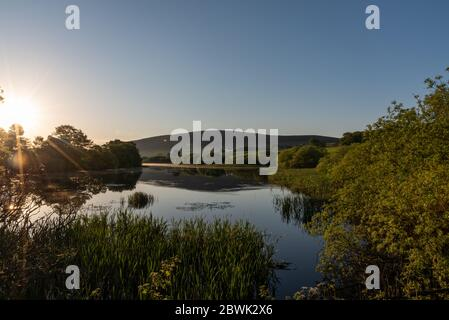 Sunrise over the lake with a farm in the background - Stock Photo