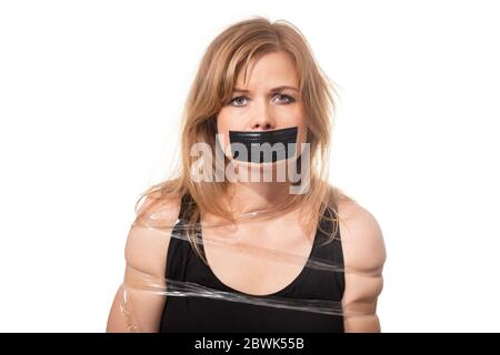 Afraid woman bound by tape and with mouth taped shut. Scared woman tied to chair become slave. Concept of forbidden opinion. male censorship. - Stock Photo