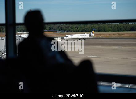 02 June 2020, North Rhine-Westphalia, Münster: One passenger is sitting in the departure hall at Münster-Osnabrück Airport. In the background a Lufthansa aircraft is on the tarmac. After the corona-induced lock-down of flight operations at Münster-Osnabrück Airport, Lufthansa is now taking off again with the connection to Munich. AIS-Airlines will follow with the route to Stuttgart. The first tourist flights are expected at the end of June at the beginning of the summer holidays in North Rhine-Westphalia. Photo: Guido Kirchner/dpa - Stock Photo