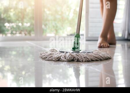 Asian women cleaning folk using mop tiles. - Stock Photo