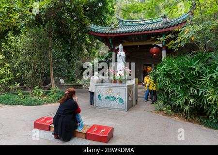 Woman praying in front of a white Guanyin statue. Inside the Nanputuo temple park. - Stock Photo