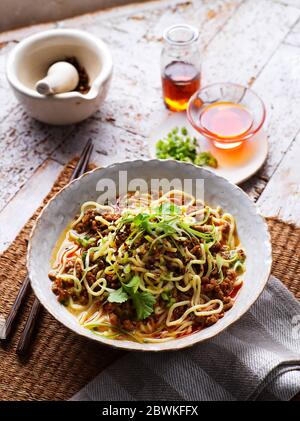 Traditional Sichuan (Szechuan) Chinese Dan Dan Noodles with Minced Pork on traditional backdrop - Stock Photo