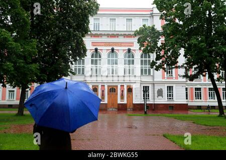 Moscow, Russia. 2nd June, 2020. A person under an umbrella walks in front of the Russian University of Transport (MIIT). Credit: Sergei Fadeichev/TASS/Alamy Live News