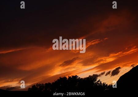 Golden sunset through wires over the roof of houses - Stock Photo