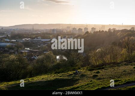 Bristol, England, UK - April 3, 2020: The sun sets behind the skyline of Bristol as viewed from Trooper's Hill park. - Stock Photo