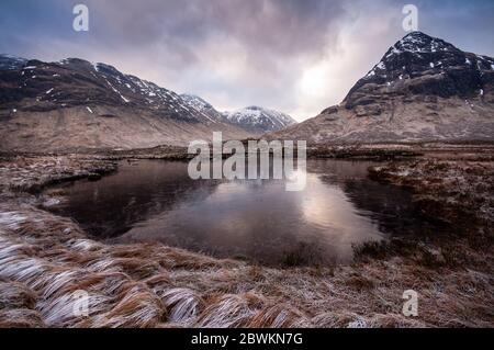 A small frozen lake stands in frost-covered moorland and under snow-capped mountains on Rannoch Moor in the West Highlands of Scotland. - Stock Photo