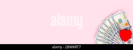 Cash money and red heart on pink background with copy space, flat lay, top view. Concept for money savings plan, or health care insurance. Mockup