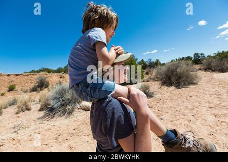 14 year old girl giving younger brother a piggyback ride, Galisteo Basin, NM. - Stock Photo
