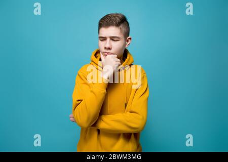 A young man in a sweatshirt looks doubtfully at an imaginary object to his left - Stock Photo