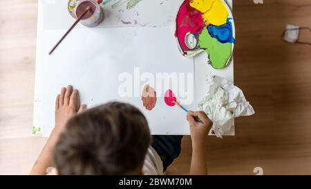 High angle view of young boy painting on paper with colorful paints.