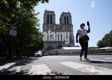 Paris, June 2. 15th Apr, 2019. A woman walks in front of the Notre-Dame Cathedral in Paris, France, June 2, 2020. The Parvis Notre-Dame was reopened to the public from May 31 after more than one year's close because of the huge fire on April 15, 2019. Credit: Gao Jing/Xinhua/Alamy Live News - Stock Photo