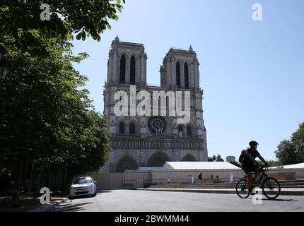 Paris, June 2. 15th Apr, 2019. A man rides a bike in front of the Notre-Dame Cathedral in Paris, France, June 2, 2020. The Parvis Notre-Dame was reopened to the public from May 31 after more than one year's close because of the huge fire on April 15, 2019. Credit: Gao Jing/Xinhua/Alamy Live News - Stock Photo