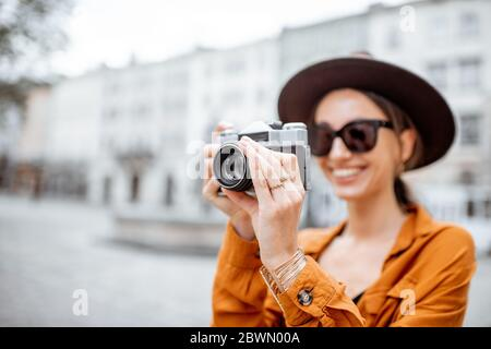 Portrait of a young stylish woman with photo camera traveling old city street. Concept of happy traveling and summer vacations in the european town - Stock Photo