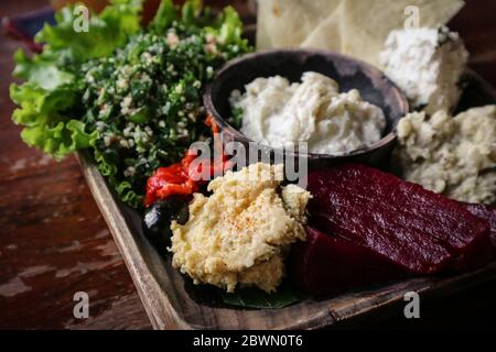 Mezze Platter with hummus, babaganoush, tabouli, roasted peppers, beet, feta cheese and kalamata olives served with pita bread - Stock Photo