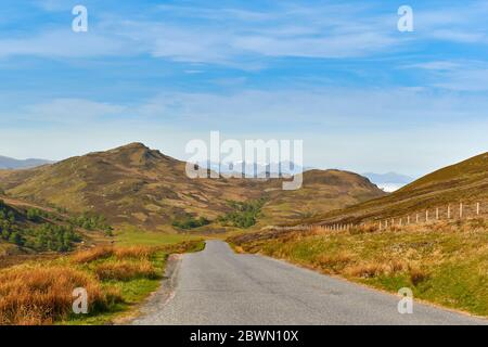 GENERAL WADE'S MILITARY ROAD ON THE SOUTH SIDE OF LOCH NESS SCOTLAND FROM HILL ABOVE LOCH TARFF LOOKING TOWARDS BEN NEVIS MOUNTAIN RANGE - Stock Photo