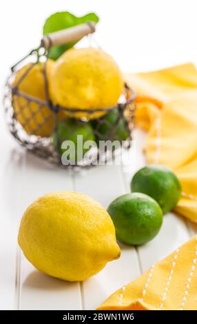 Organic lemons and limes in a basket on white background - Stock Photo