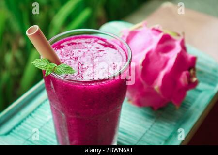 Dragon fruit smoothie in glass on table in tropical cafe outdoor - Stock Photo
