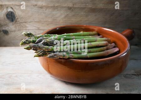 Organic green asparagus (Asparagus officinalis) fresh from the market in a brown ceramic bowl on a rustic wooden board, copy space, selected focus, na - Stock Photo