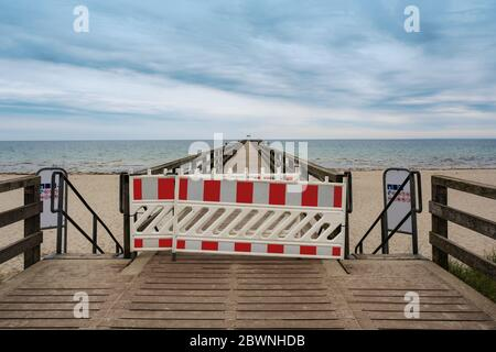 Closed pleasure pier at the Baltic sea beach during the coronavirus pandemic in the popular tourist resort Boltenhagen, Germany, copy space, selected - Stock Photo