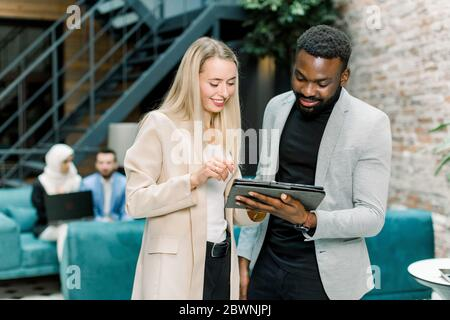 Front view of successful smiling young multiracial business people, Caucasian woman and African bearded man, standing in the office room and talking - Stock Photo