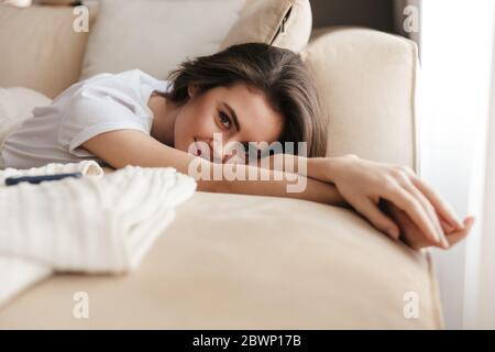 Beautiful smiling young brunette woman relaxing on a couch at home, looking at camera - Stock Photo