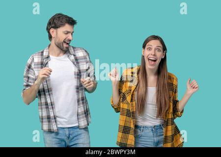 Young guy and girl having fun dancing with open mouths.