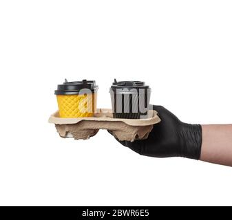 hand in a black latex glove holds a paper tray with disposable cardboard cups and plastic covers on a white background, safe and contactless delivery Stock Photo