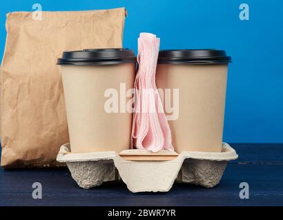 brown paper disposable cups with a plastic lid stand in the tray on a blue wooden table, takeaway containers. - Stock Photo