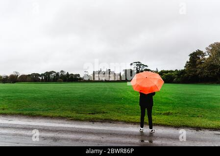 Unidentified woman with red umbrella in Muckross House and gardens against cloudy sky. It is a mansion located in the The National Park of Killarney. - Stock Photo